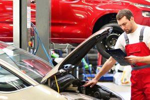 Kundendienst in einer Autowerkstatt - Mechaniker kontrolliert Fahrzeug
